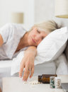 Woman sleeping in bed with pills in foreground closeup of a mature at home Royalty Free Stock Images