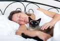 Woman sleeping in embrace with cat