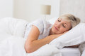 Woman sleeping with eyes closed in bed pretty mature the Stock Photo