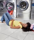 Woman sleeping on floor at laundry young african american Stock Images
