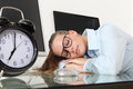 Woman sleeping on work in office desk with clock