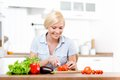 Woman slices groceries for salad cuts sitting at the kitchen table Royalty Free Stock Image
