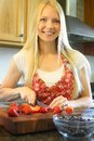 Woman slicing strawberries an attractive happy young is chopping in her kitchen Royalty Free Stock Photo