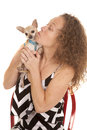 Woman small dog chevron dress kiss a in her stitting and loving on her little puppy Stock Image