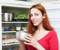 Woman with small pan near opened refrigerator Stockfotografie