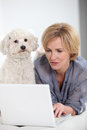 Woman by small white dog on laptop computer accompanied Stock Photos