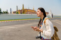 Woman on smart phone walking on grand palace Royalty Free Stock Photo