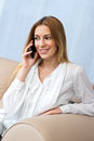 Woman with smartphone in her home attractive sitting on the sofa Stock Image