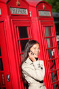 Woman on smartphone by london red phone booth taking young casual female business having conversation mobile smart Stock Images