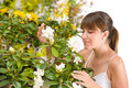 Woman smelling blossom of Rhododendron flower Royalty Free Stock Photo
