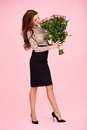 Woman smelling a bunch of roses full length portrait beautiful smiling as she smells large pink she is holding in her hands Royalty Free Stock Images