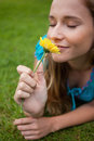Woman smelling a flower while lying on the grass Royalty Free Stock Photo
