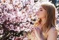 Woman smelling flowers in blooming sakura garden Royalty Free Stock Photo
