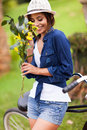 Woman smelling flowers cheerful cute young outdoors Stock Photos