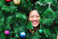 Woman smile behind christmas tree Royalty Free Stock Photo