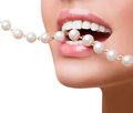 Woman smiles showing white teeth, holding a pearly necklace into the mouth Royalty Free Stock Photo