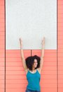 Woman smiling and pointing to blank poster portrait of a happy young Royalty Free Stock Images