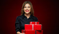 Woman smiling with teeth holding red gift box.