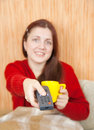 Woman smiling with TV remote Royalty Free Stock Photography