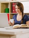 Woman smiling while using a laptop photo of beautiful and drinking coffee at home or at her office Stock Images