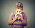 Woman sneezing blowing her runny nose Royalty Free Stock Photo