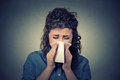 Woman sneezing in a tissue blowing her runny nose Royalty Free Stock Photo