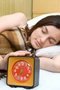 Woman snoozing a red alarm clock Stock Images