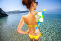 Woman with snorkeling mask near the sea in swimsuit standing back view focused on Royalty Free Stock Images