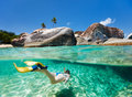 Woman snorkeling at tropical water split photo of young in turquoise among huge granite boulders the baths beach area major Stock Photo