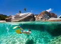 Woman snorkeling in tropical water split photo of young turquoise among huge granite boulders at the baths beach area major Stock Image