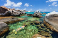 Woman snorkeling at tropical water young in turquoise among huge granite boulders the baths beach area major tourist attraction on Stock Images