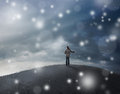 Woman in snow storm a standing on top of a hill a Stock Image