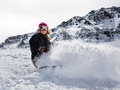 Woman snowboarder in motion in mountains Royalty Free Stock Photo