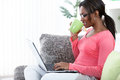 Woman in a sofa with laptop black using while having tea her living room Royalty Free Stock Image