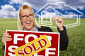 Woman with sold for sale sign keys and ghosted house very happy real estate in hand behind her Royalty Free Stock Photography