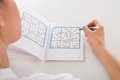 Woman solving sudoku Royalty Free Stock Photo