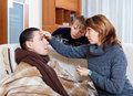 Woman and son caring for unwell man men who has high temperature in living room Royalty Free Stock Photo