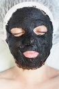 Woman in spa salon with black mud face mask Royalty Free Stock Photo