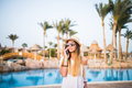 Woman speak on phone relaxing near swiming pool. Summer vocation. Royalty Free Stock Photo