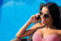 Woman speaking by phone on deckchair smiling pretty talking the outdoors Stock Photo