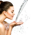 Woman with splashes of water beautiful in her hands Stock Image