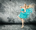 Woman in splashing turquoise dress sexy on concrete wall background Stock Photos