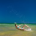 Woman splashing water in the ocean yong happy Royalty Free Stock Photography