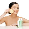 Woman with sponge picture of and cosmetic bottles Royalty Free Stock Image