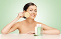 Woman with sponge picture of and cosmetic bottles Royalty Free Stock Photos