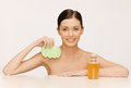 Woman with sponge picture of and cosmetic bottles Royalty Free Stock Images