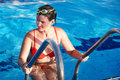 Woman in sport goggles leaves swimming pool. Stock Image