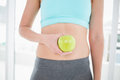 Woman in sportswear holding apple on her toned belly bright fitness studio Stock Photography