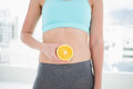Woman in sportswear holding orange on her toned belly Stock Photography
