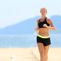 Woman in sportswear running at beach young caucasian determined slim female is jogging on sunny day she is representing healthy Stock Photo